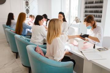 Group of girlfriends, manicure in beauty salon