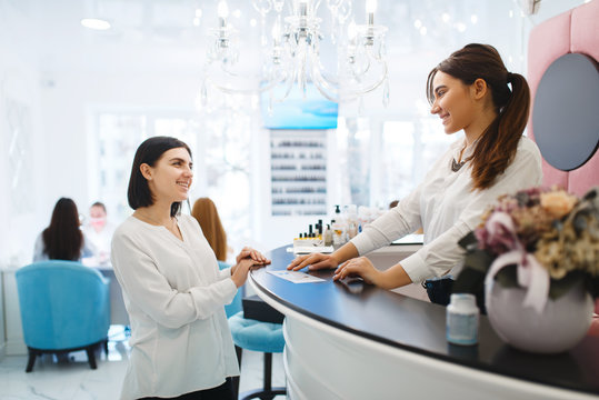 Woman talks with administrator of beauty salon