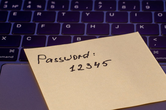 A very weak, simple and widespread password is written on a sticker that lies on the laptop keyboard. Password Security Weakness Concept. Bad password. Typical information security failures.