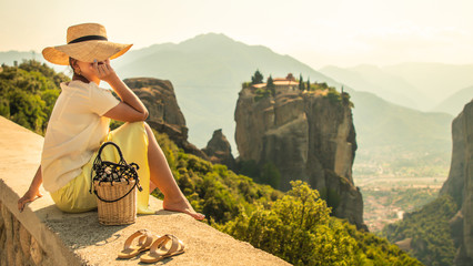 Young woman with white dress and large hat sitting in front of greece meteor mountains, monastery and village in the background Fototapete