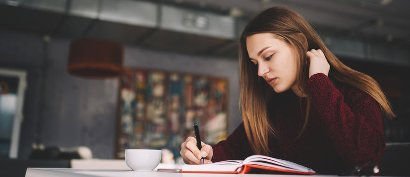 Attractive young talented writer 20 years old creating new book atricles while sitting at cafeteria, thoughtful student preparing for important college exam writing answers for question in notebook