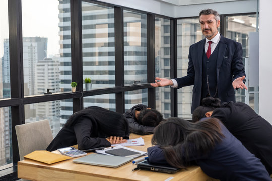 Boss bored and looking down at lazy colleague sleeping on table in meeting room