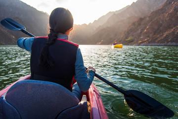 Aluminium Prints Dubai Woman kayaking in Hatta lake in Dubai at sunset