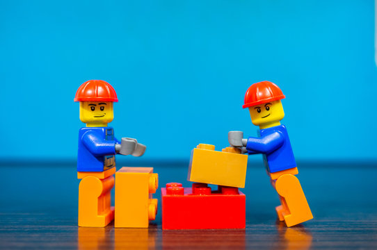 Two Lego construction workers build something together out of plastic bricks on December 14, 2019 in Poznan, Poland.