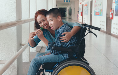 Mother and Asian special child on wheelchair is smile happily on background in school corridor, Life in the education age of disabled children, Happy disabled kid concept..