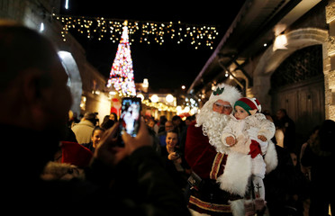 People take a photo with a man wearing a Santa Claus outfit as they attend a Christmas tree lighting ceremony at Jerusalem's Old City