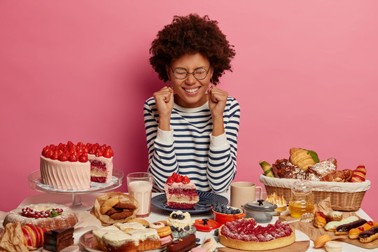 Positive curly woman clenches fists, keeps eyes closed, dressed in striped jumper, has big piece of cake on plate, surrounded with various sweet desserts, addicted to sugar isolated on pink background