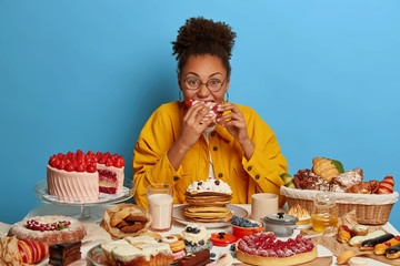 Funny glutton woman bites cakes with big appetite, cant stop eating sweet desserts, being in mood for enjoying sugary freshly baked bakery, surrounded by sweet treasures, has yummy snack, feels hunger