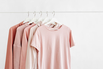 Feminine clothes in pastel pink color on hanger on white background. Spring cleaning home wardrobe. Minimal fashion concept. Wall mural