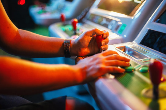 Detail on hands playing with joystick on old vintage arcade game in a dark room for playing video games