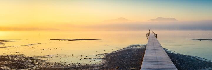 Foto auf AluDibond Orange Sonnenaufgang am See mit Steg und Nebel - Chiemse Panorama