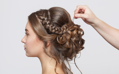 Portrait of a beautiful sensual light brown haired woman with a wedding hairstyle in a beauty salon. The hairdresser does the hairstyle. Wedding hairstyle.