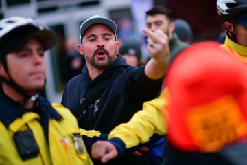 A Trump supporter makes a profane gesture to protesters chanting outside Lincoln Financial Field due to the visit by U.S. President Donald Trump at the Army-Navy football game in Philadelphi