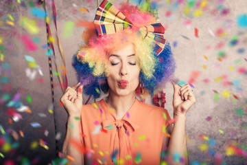 Deurstickers Carnaval Englisch beautiful young woman with colorful afro wig and colorful carnival make-up and confetti