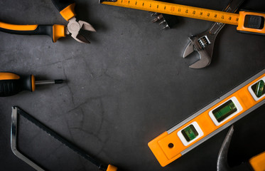 set of black and orange tools on black concrete background