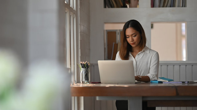 Businesswoman working her home office with laptop computer.