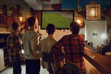 A group of people watching tv football in a sports bar.