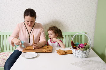 Mom glues the details gingerbread house with protein cream while her daughter looks. Pastry bag with cream in her hands