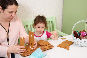 Mom glues the details gingerbread house with protein cream while her daughter looks.