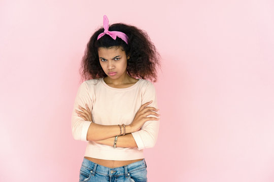Sad angry serious young african american teenage girl mixed race woman pout lips sulking look at camera. stand arms crossed feel offended face isolated on pink studio background