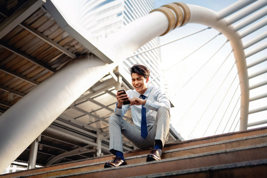 Happy Young Businessman Sitting on Staircase and Using Smartphone. Urban Lifestyle. Low Angle View. Modern Buiding in City as background