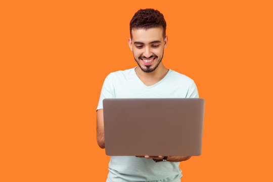 Portrait of cheerful young brunette man with beard in white t-shirt typing email on laptop and smiling, reading positive message or surfing the web. indoor studio shot isolated on orange background