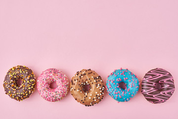 Different types of a colorful donats decorated sprinkles and icing on pastel pink background
