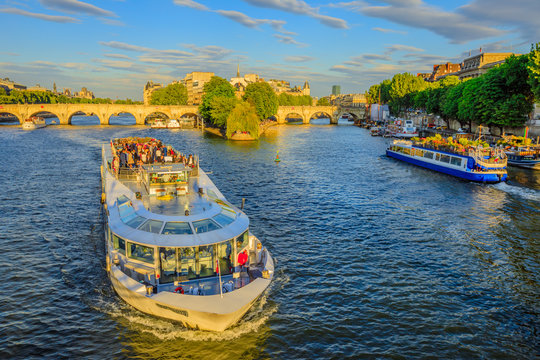 Paris, France - July 1, 2017: Tourist cruise on Seine river. Bateau mouche from Pont Neuf bridge and Notre Dame church on background. Aerial view of touristic cruise from the Pont des Arts at sunset.