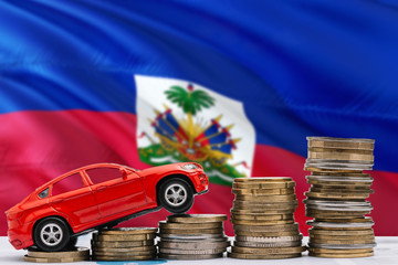 Haiti savings concept. Money for new automobile, toy car and coin piles standing on national flag background. Copy space for text.