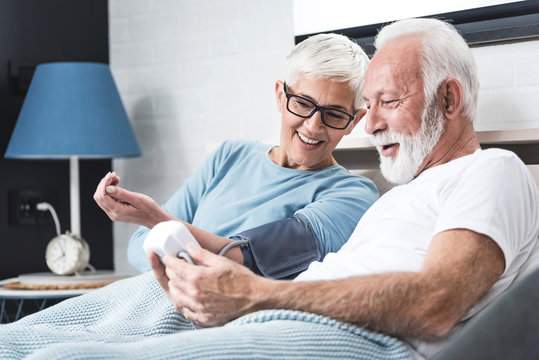 Ederly couple measures blood pressure
