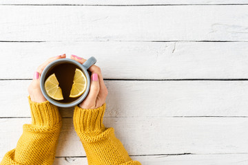 Printed roller blinds Tea Female hands in warm sweater holding cup of tea with lemon on white wooden table. Top view
