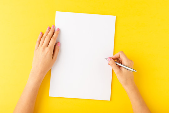 Overhead shot of woman's hands writing on empty white sheet of paper. Close up