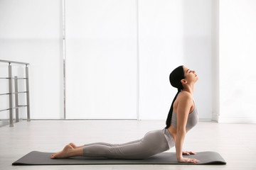 Young woman practicing cobra asana in yoga studio. Bhujangasana pose