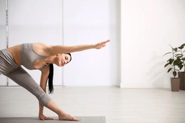 Young woman practicing triangle asana in yoga studio. Utthita Trikonasana pose