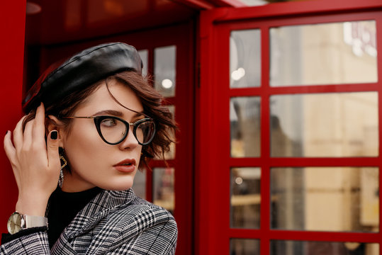 Fashionable, elegant woman wearing glasses, trendy leather beret, hand watch, classic autumn coat, posing near red call box in street of city. Copy, empty space for text
