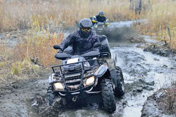 Cool pictures of active ATV driving in mud and water at Autumn weather