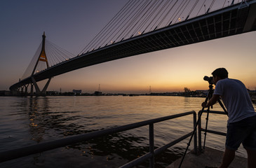 silhouette of photographer taking picture of bridge during sunset