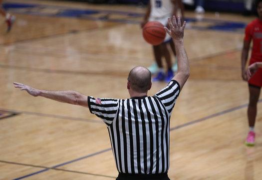 A basketball referee signals a foul
