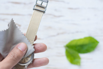 Close up cleaning modern watch with microfiber cloth and Cleaner cream concept.Cleaning modern watch by Cleaner cream.Cleaning stainless steel by Cleaner cream,Cleaning leather by Cleaner cream,