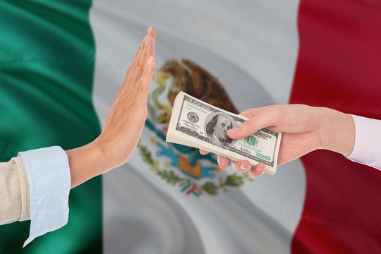 Mexico bribery refusing. Closeup of female hands extending a pile of dollar bills to the male hands gesturing as if rejecting the money.