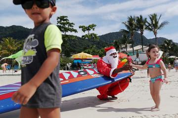 Carlos Bahia, dressed as Santa Claus, greets children at the Maresias beach in Sao Sebastiao, hometown of WSL World Champion Gabriel Medina