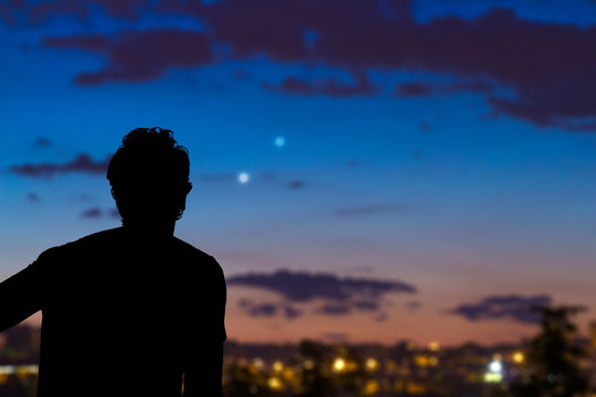 Man looking at the night sky from urban area.