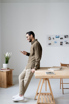 Young business employee in casualwear scrolling in smartphone by workplace