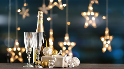 Fototapeten Alkohol Champagne with gift and decor on table against blurred lights