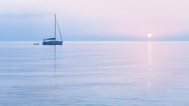 Tender pastel pink sun and sailing boat in blue morning haze color sunrise with blue waters. Travel and vacation destination concept or peace and tranquility concept banner with copy space