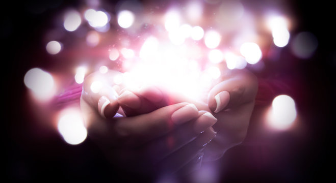 Magic particles on the palms, magic, witchcraft. Magic in female hands. There is light in female hands. Abstract bokeh light background.