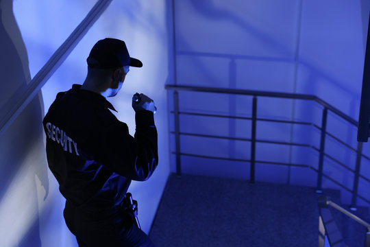 Male security guard with flashlight on stairs in darkness