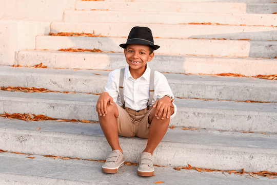Cute fashionable African-American boy sitting on stairs outdoors