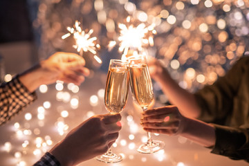 Papiers peints Bar Hands of couple with flutes of champagne and their friends with bengal lights