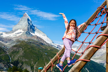 Wall Mural - Portrait of a cute little girl in mountains, wearing grey pullover, Switzerland
